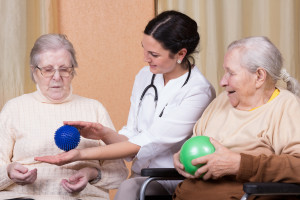 Nurse helping women roll fitness balls